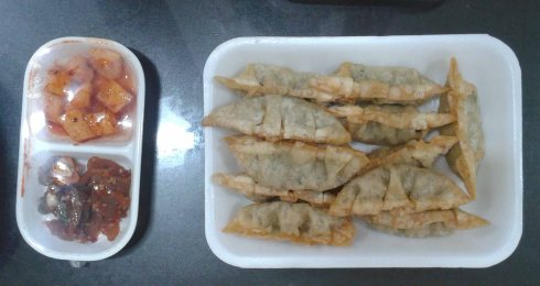 Mandu: fried dumplings filled with pork, tofu, vegetables and noodles Side dish: kimchi radish and pickled radish